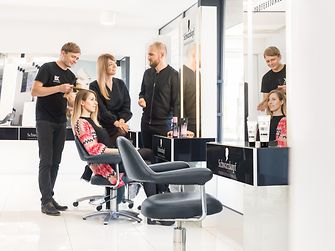 salon owner is discussing the new BC Fibre Force product range with Henkel employees after applying it to his client's hair.